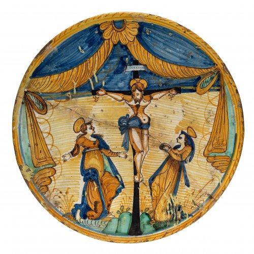 Platte. Majolika, farbige Malerei. Christus am Kreuz unter Vorhangdraperie. Deruta oder Montelupo, 16./ 17. Jh. ø40 cm.