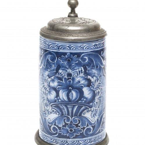 Walzenkrug. Nürnberg, 18. Jh., Kordenbusch-Werkstatt. Fayence. Zinndeckel. Blaumalerei Schauseitig Blumenvase. Alterungsspuren. H. 22 cm.