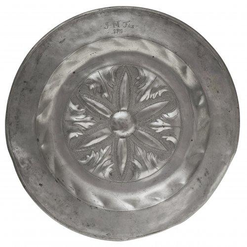 Zinnplatte. Im Fond geflechelte Blütenrosette. Besch. Besitzermonogramm von 1701. ø39 cm.