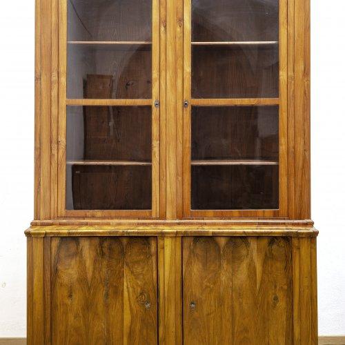 Bibliotheksvitrine. Süddeutsch, um 1830. Nussbaum furniert. 235 x 160 x 65. Zweitüriger Aufsatz.