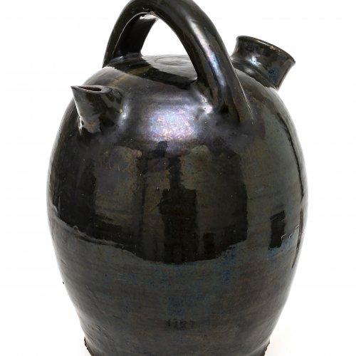 Bauchige Rohrkanne mit Bügel, Irdenware, dunkelbraun glasiert, H. 37 cm.