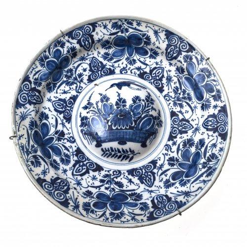 Buckelplatte. Delft, 18. Jh., Fayence. Florales Dekor in blauer Scharffeuermalerei. Zusätzlich mit Wandhalterung. Best. und rest. ø 36 cm.