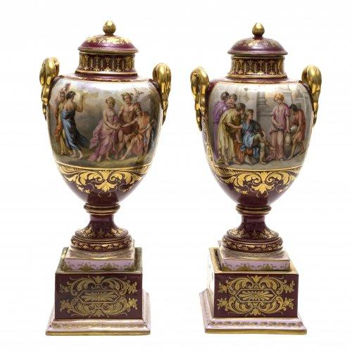 Ein Paar Potpourri-Vasen. In der Art von Wien. Porzellan. Jeweils zwei große antikisierende Szenerien, umgeben von goldenem Reliefdekor auf dunkelrotem Grund. Seitlich Henkel in Schlangenform. Abrieb des Goldes. Unterseitig Marke
