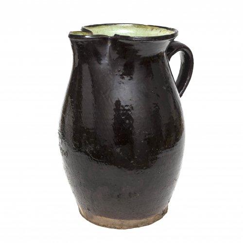 Schlanke Kanne. Oberösterreich, Irdenware, schwarz-braune Glasur, innen grünlich. Leicht besch. H. 31,5 cm.